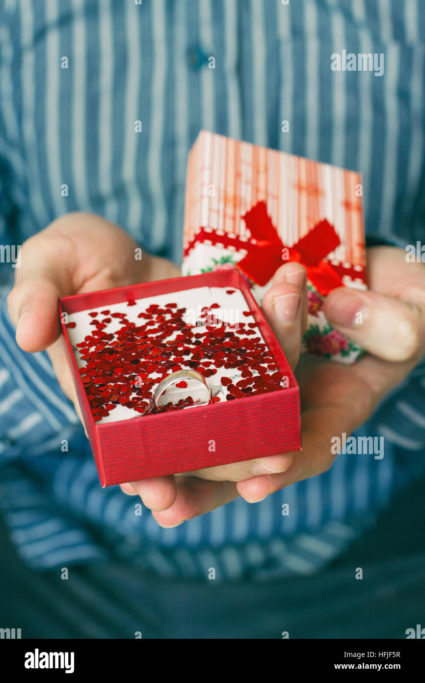 Man with a gift box in his hands with a silver ring - Stock Image