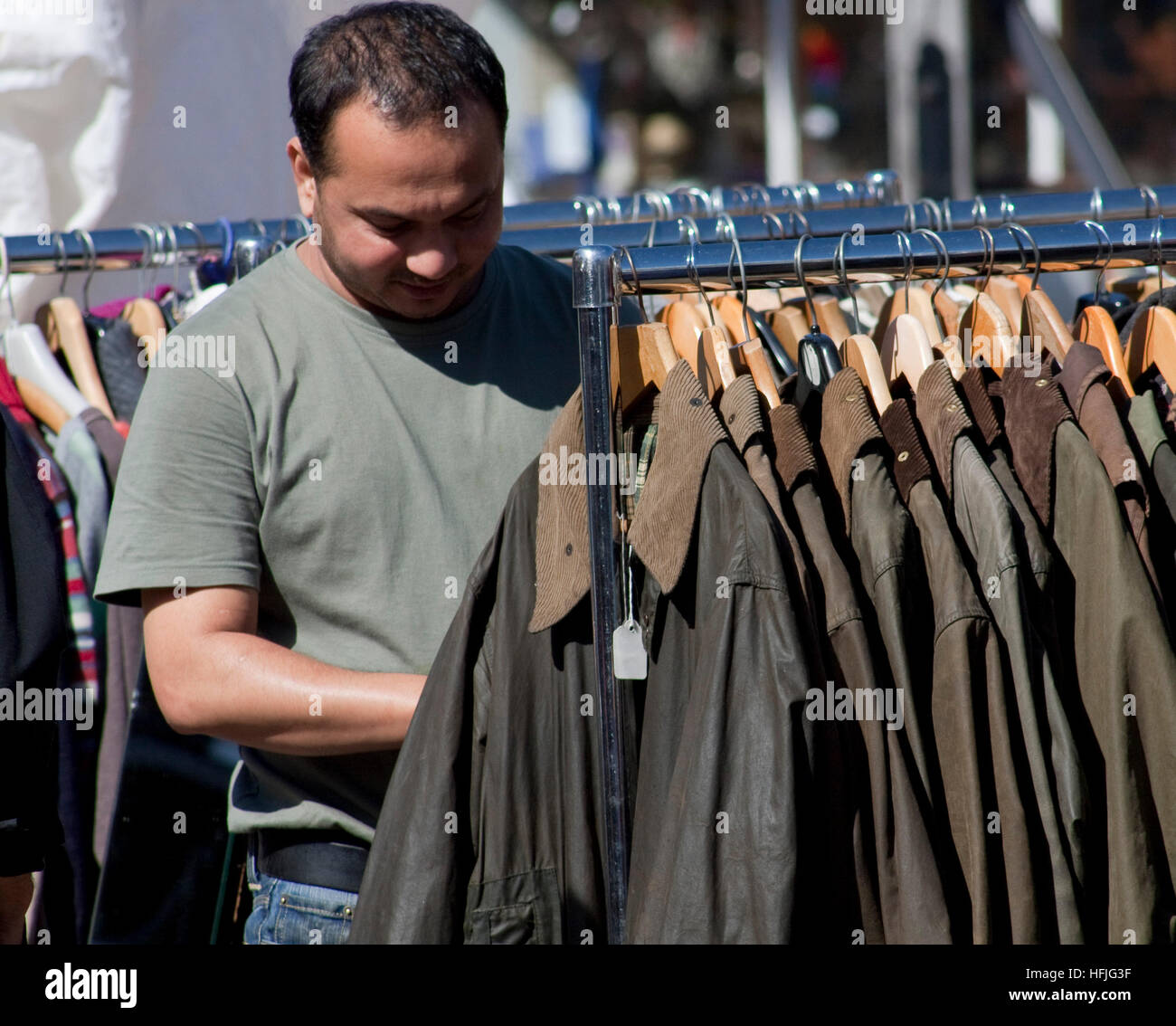 At a street market a man looking a rack of waxed jackets Stock Photo