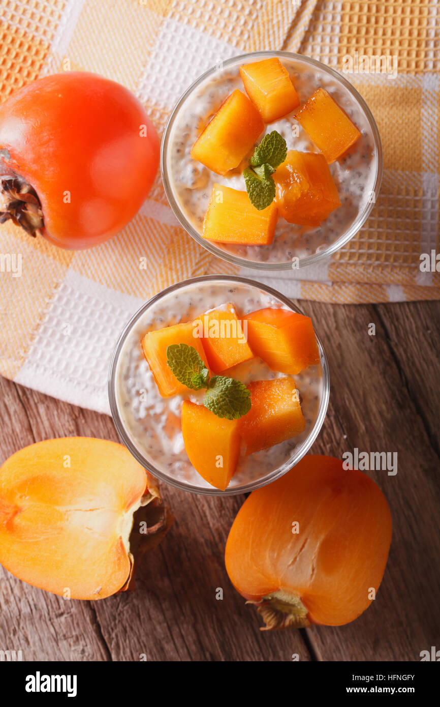 Yogurt with chia seeds and persimmon close-up on the table. vertical top view - Stock Image