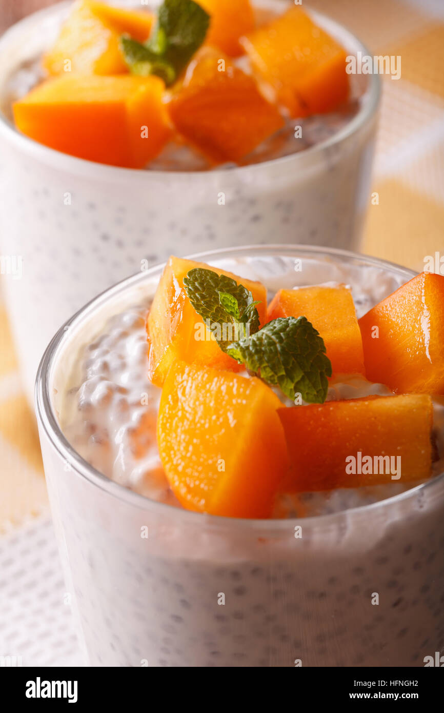 Chia seeds with yogurt and persimmon in a glass macro. Vertical - Stock Image