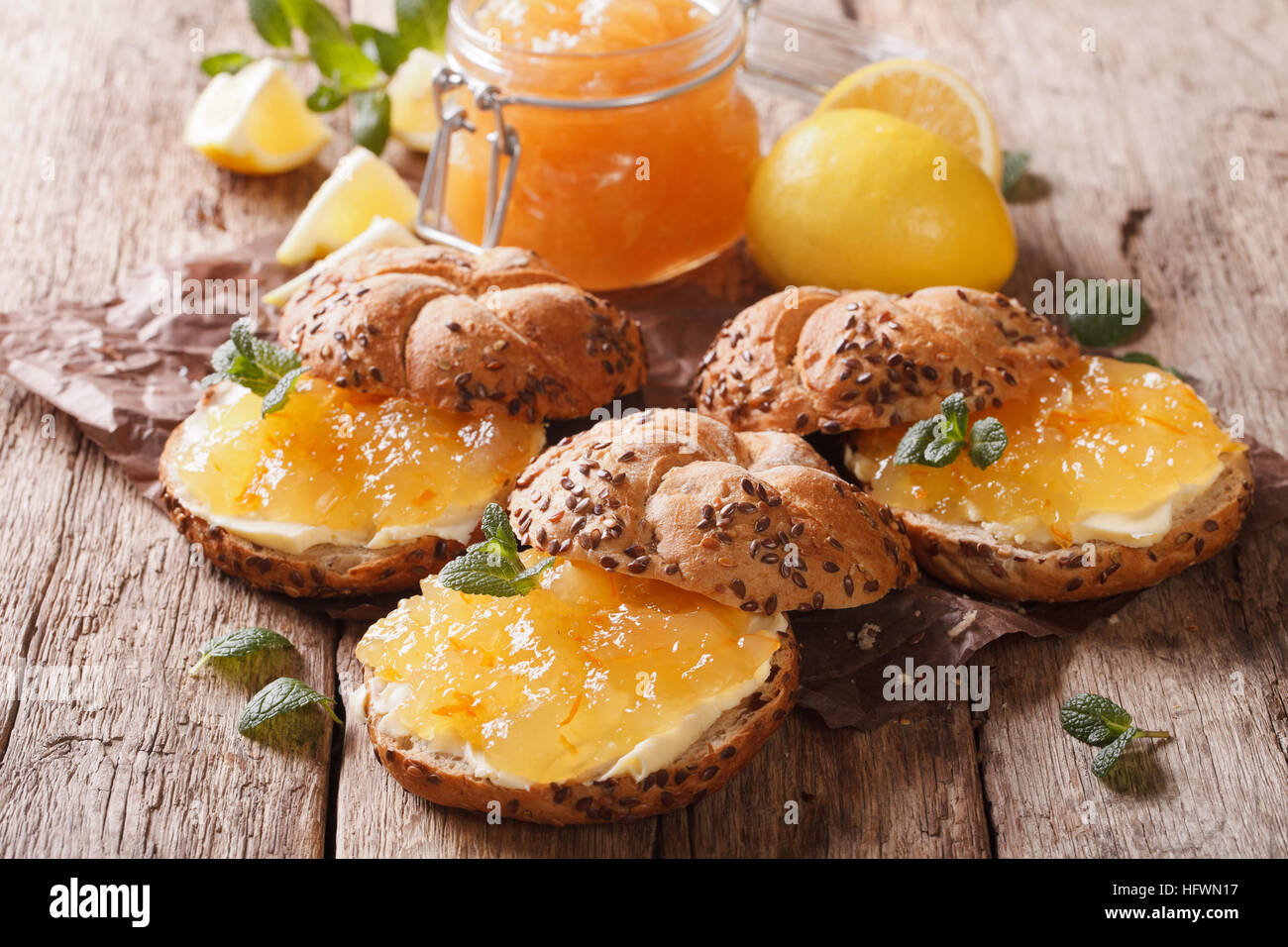 Sweet sandwiches with lemon marmalade, mint and butter on the table close-up. Horizontal - Stock Image