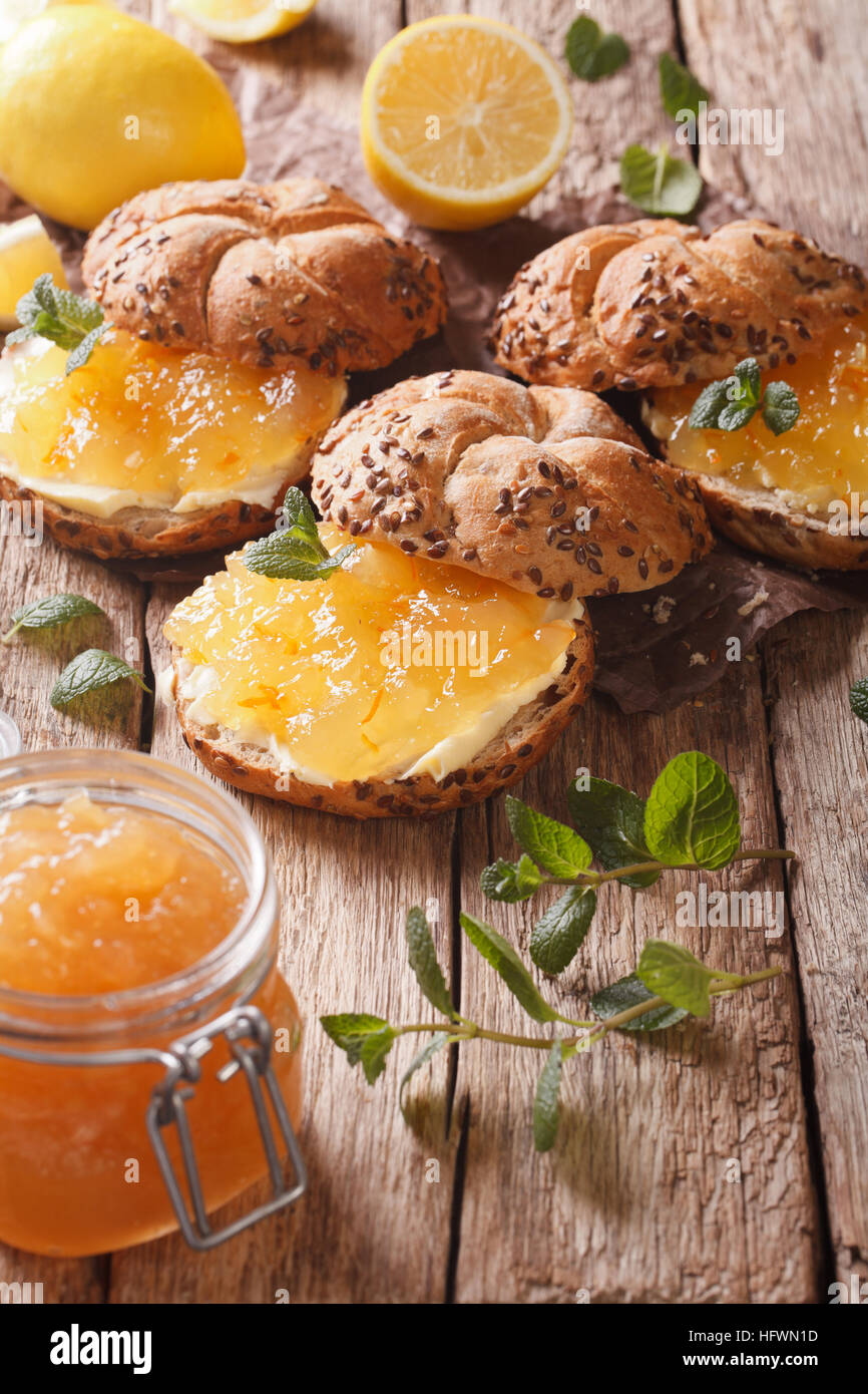 Sweet sandwiches with lemon marmalade, mint and butter on the table close-up. vertical - Stock Image