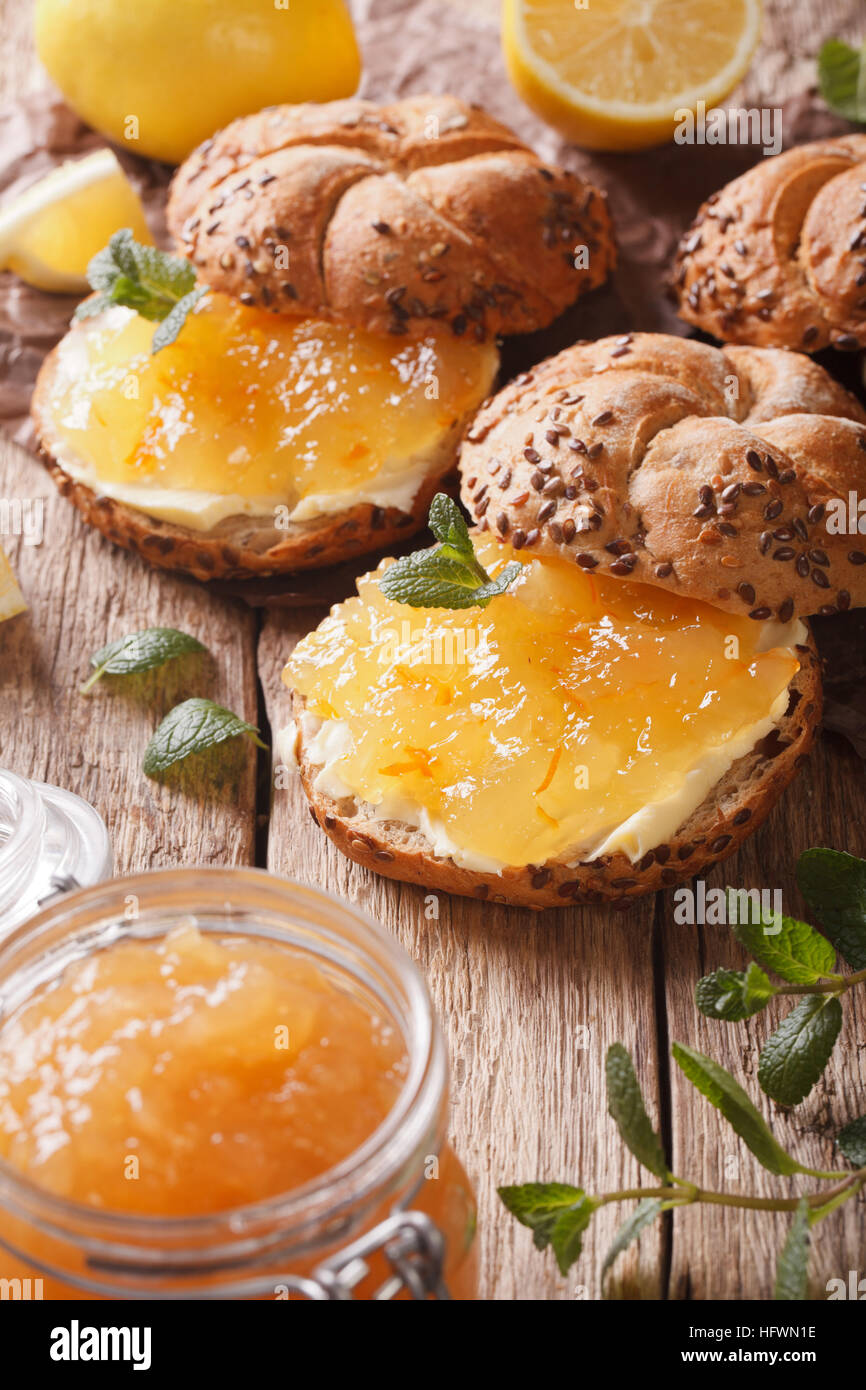 Sweet buns with lemon marmalade and butter on the table macro. vertical - Stock Image
