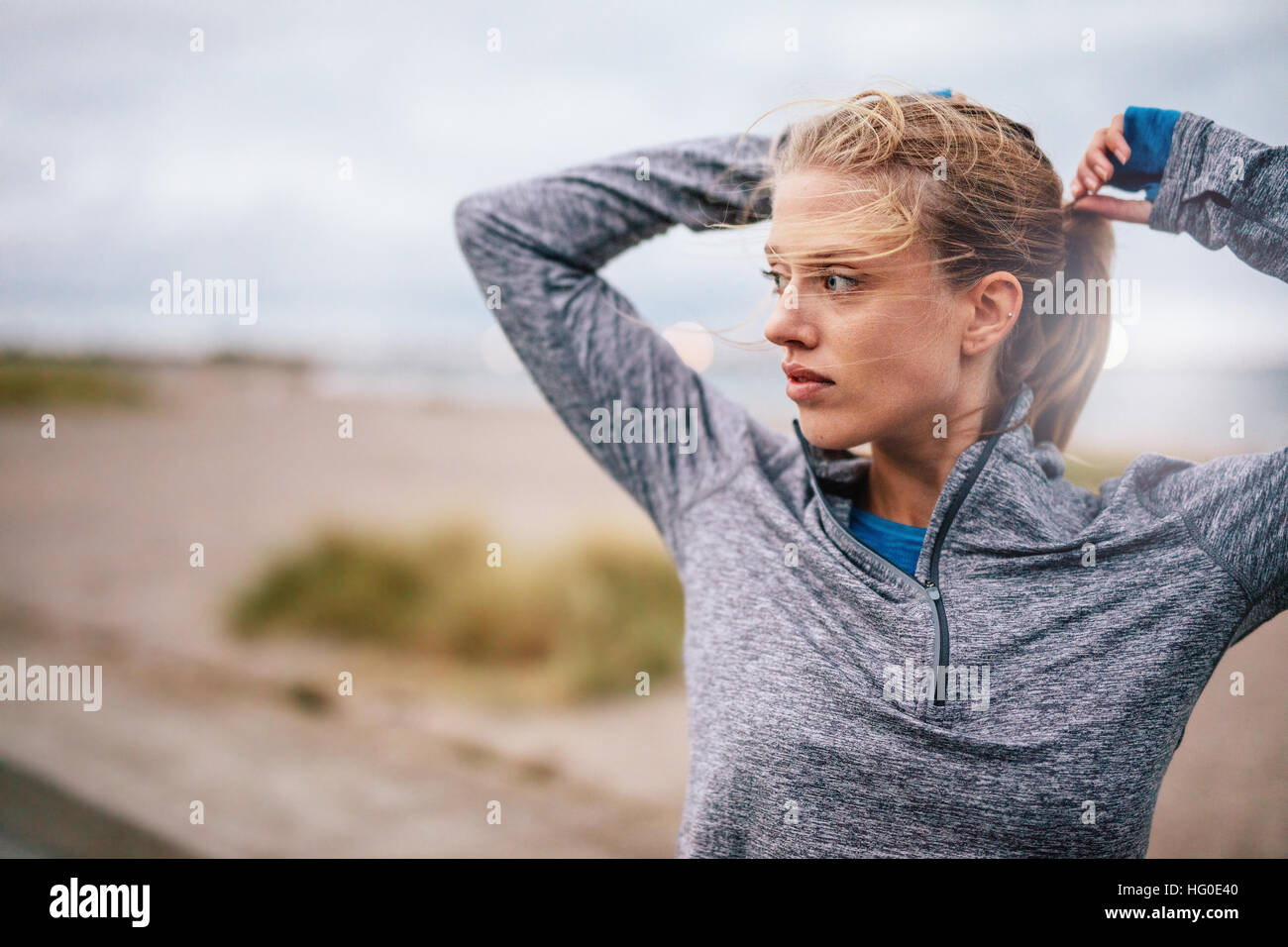 Close up of young female runner tying up hair before a run. Sporty fitness woman on outdoor workout looking away. - Stock Image