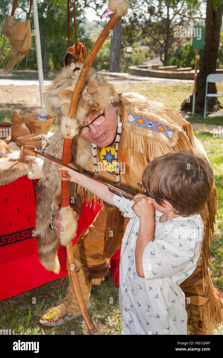 Dressed as an old time Native American Mission Indian, a historical re-enactor explains a bow and arrow to a boy - Stock Image