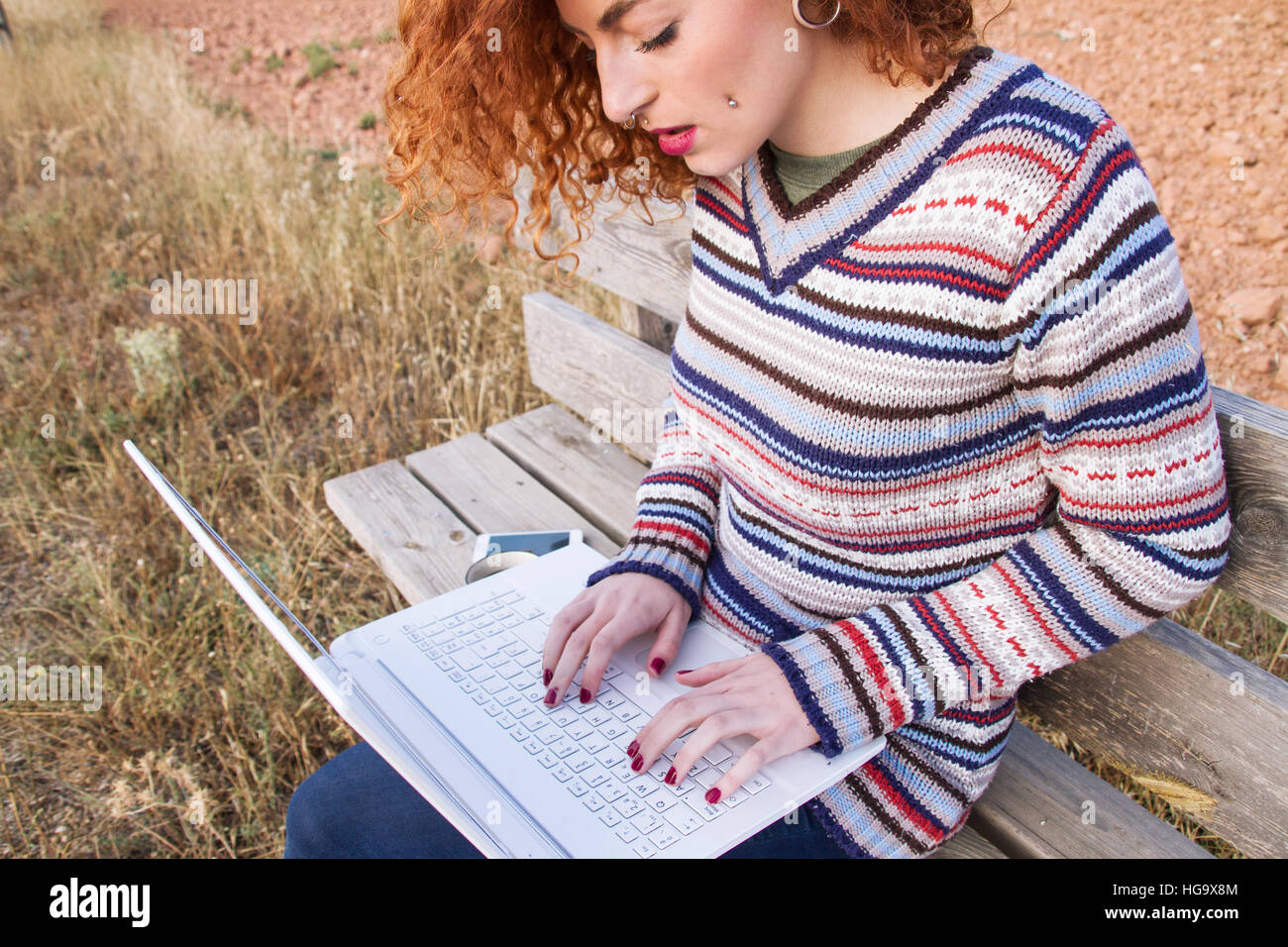 Young redhead freelance woman working with her laptop - Stock Image