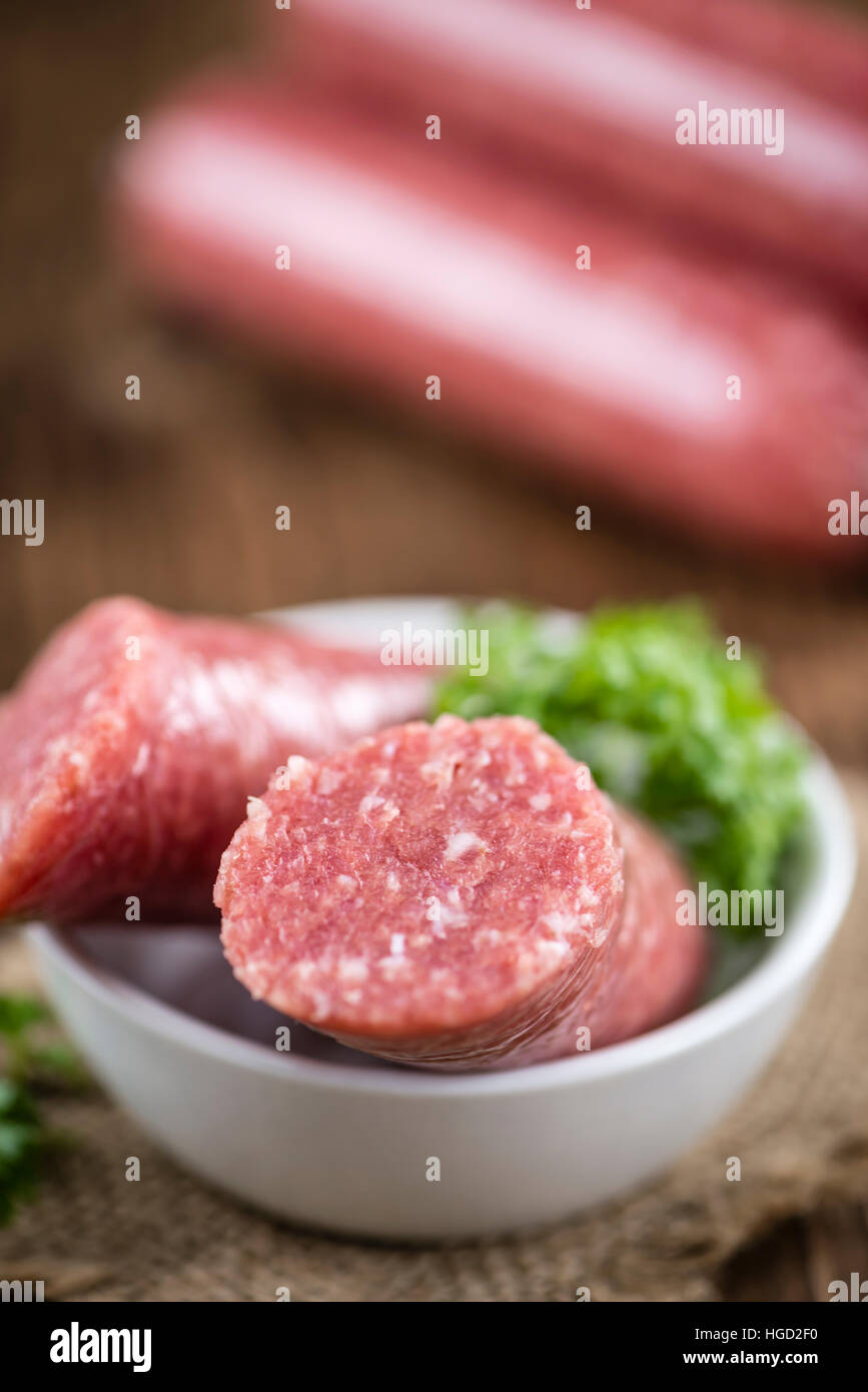 German Mettwurst (selective focus; detailed close-up shot) on wooden background - Stock Image