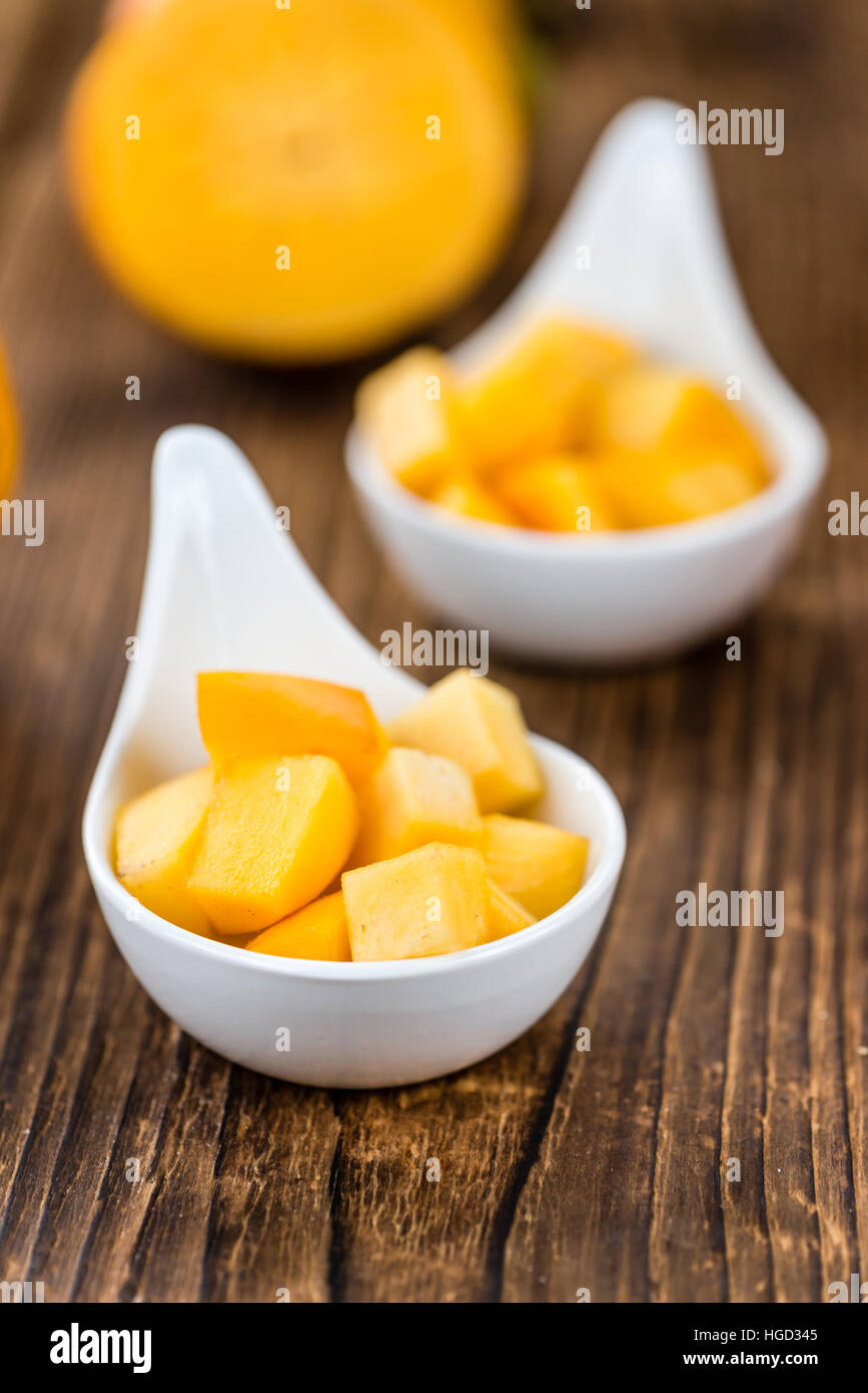 Kaki fruits on rustic wooden background (close-up shot) - Stock Image