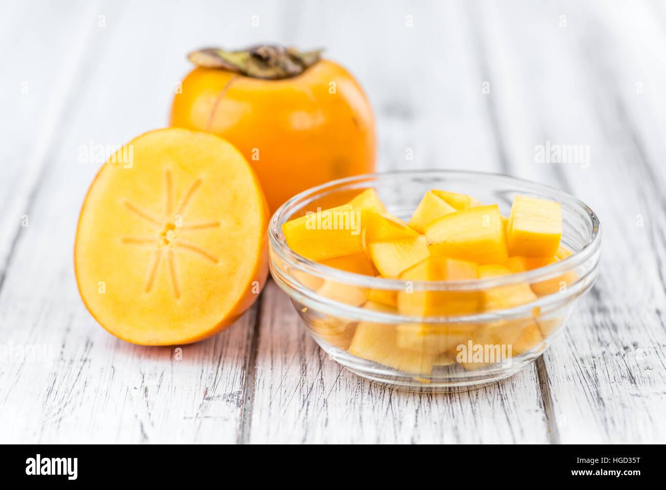 Portion of fresh made Kaki fruits (close-up shot; selective focus) - Stock Image