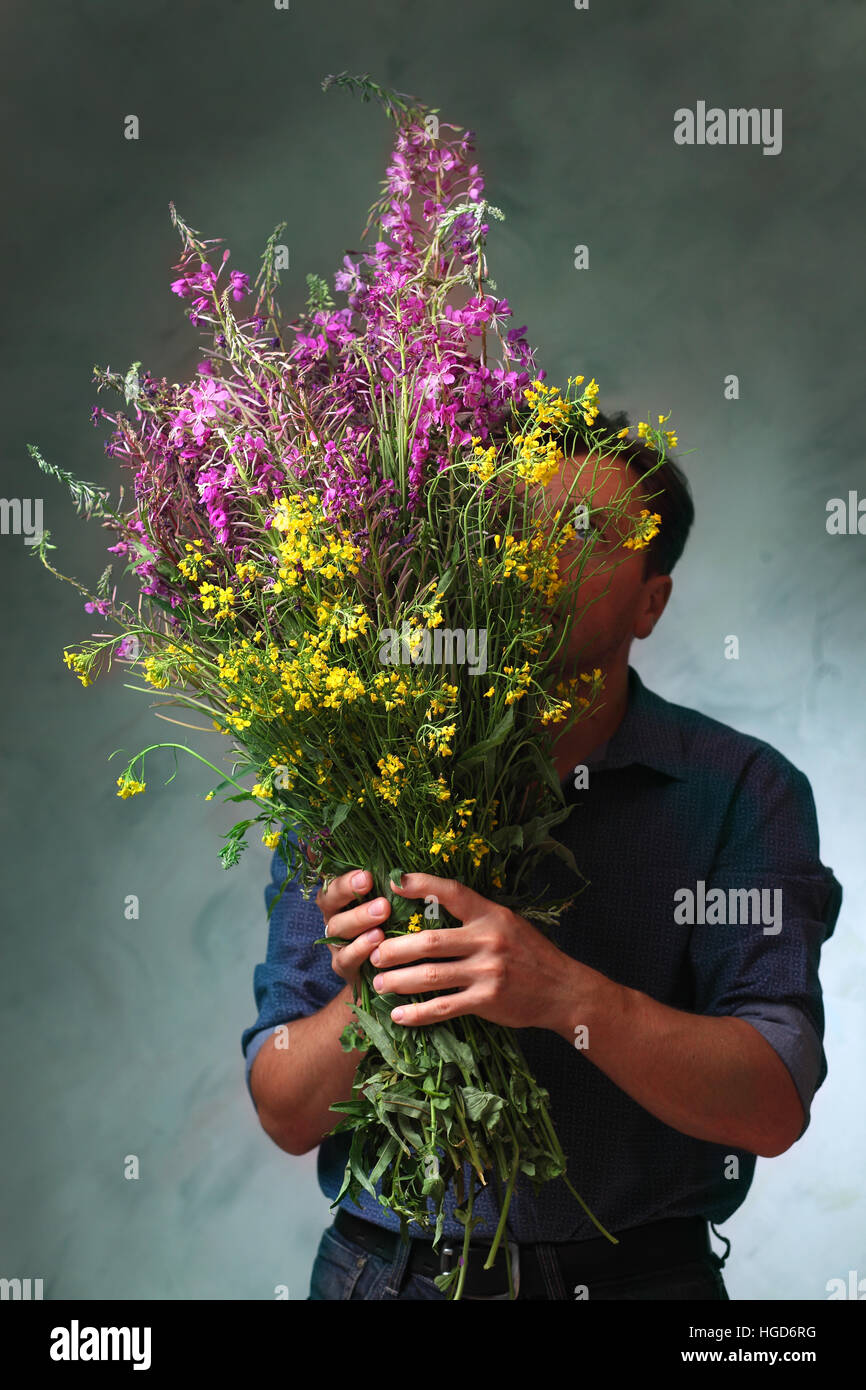 man holding a huge bouquet of wildflowers, a man came out on a date ...