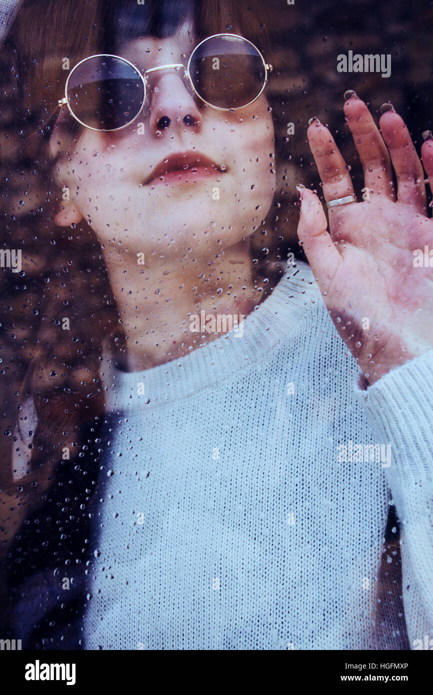 Portrait of a young woman in a rainy day through a window - Stock Image
