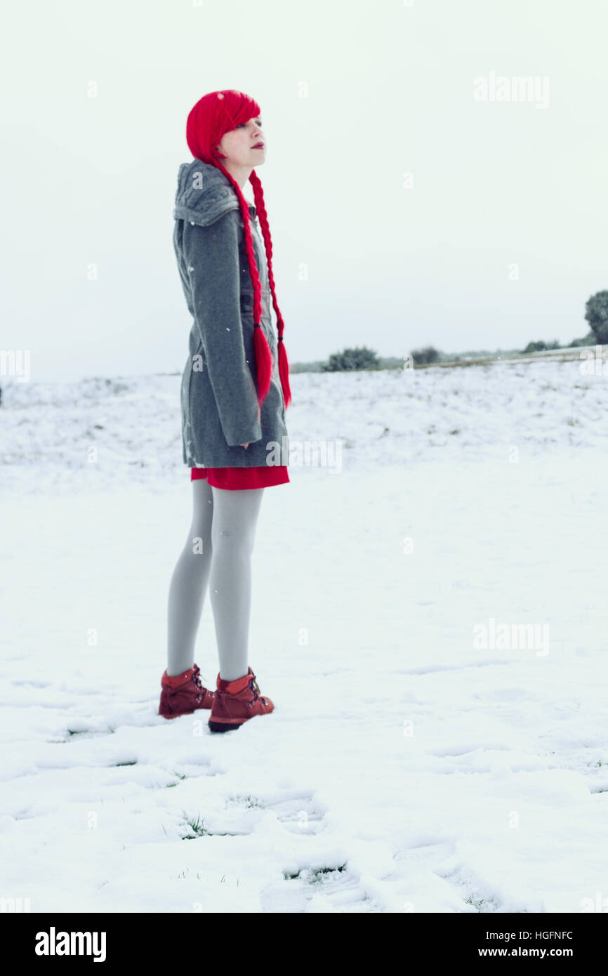 Young woman with red hair and winter clothes in a winter snowy day - Stock Image
