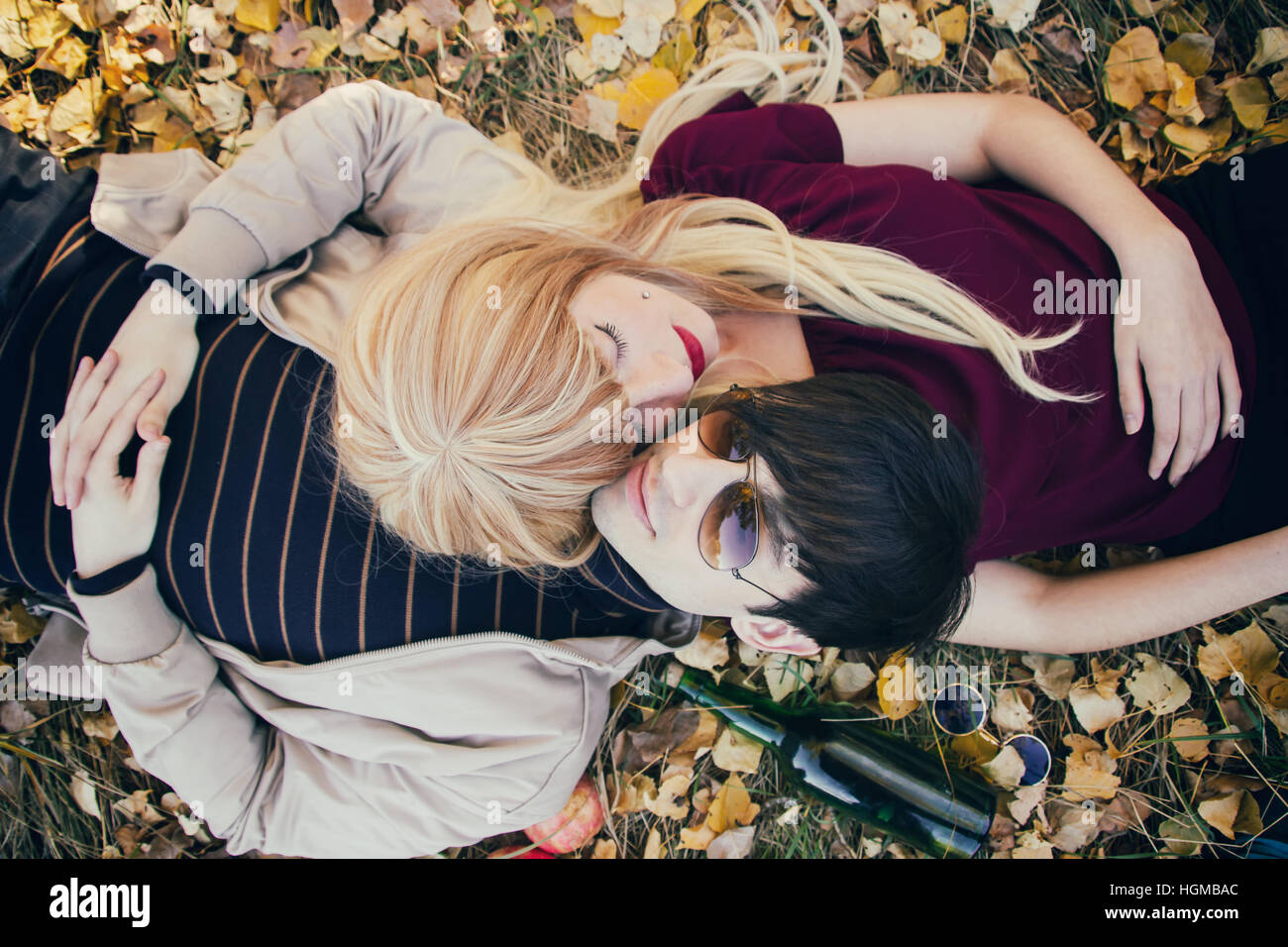 Young couple lying on the floor in a park in autumn - Stock Image