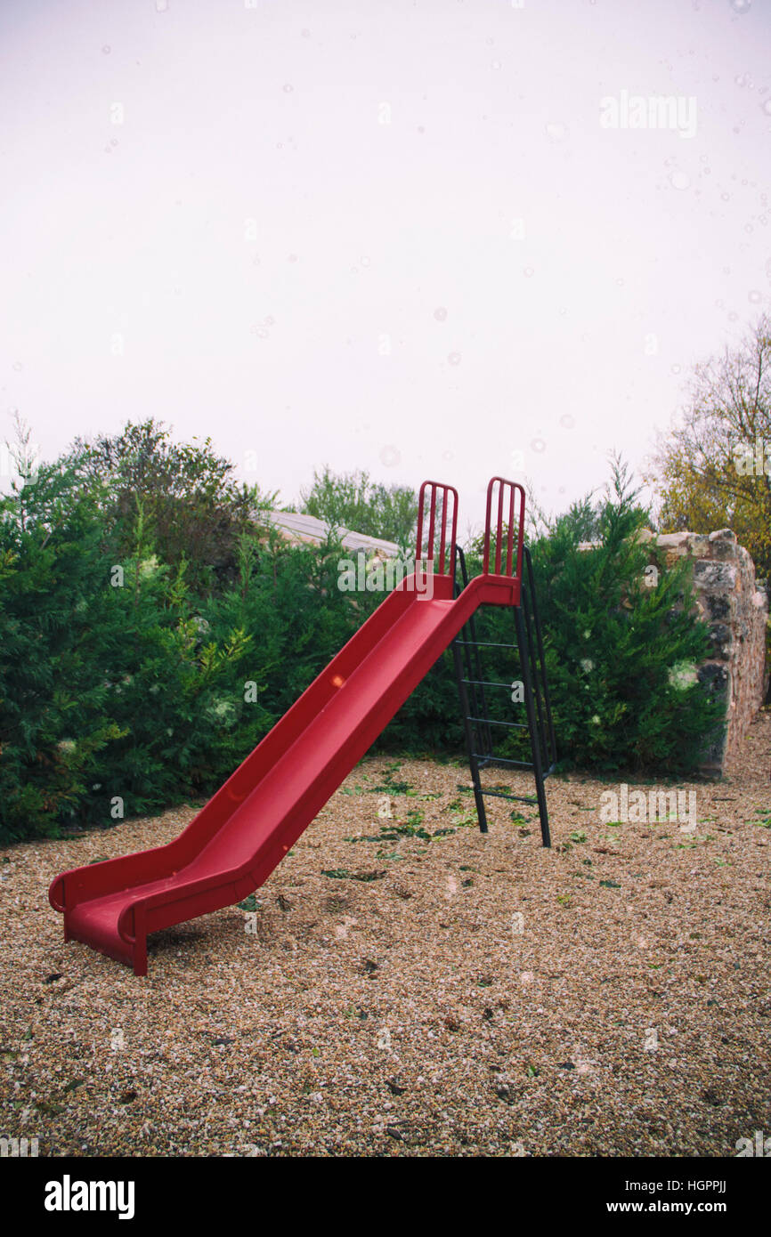 Red slide in a park - Stock Image