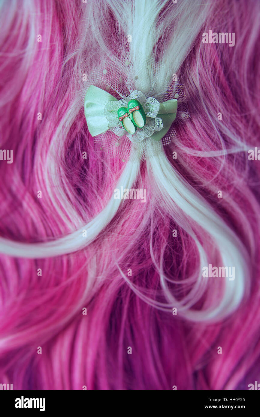Pink and white hair with a cute hair bow tie - Stock Image