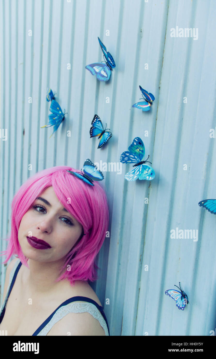 Dreamy portrait of a young woman with pink hair and a lot of blue butterflies flying around her - Stock Image