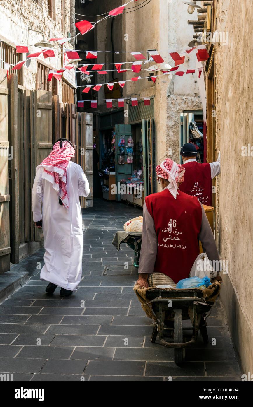 Traditionally dressed Arab man walking in the Souq Waqif, Doha, Qatar - Stock Image