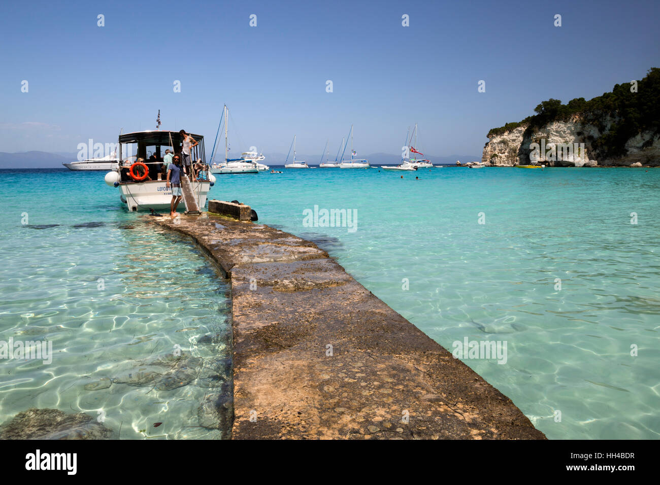 Pier and boat on Voutoumi beach, Antipaxos, Ionian Islands, Greek Islands, Greece, Europe - Stock Image