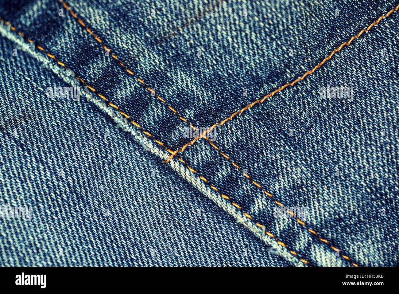Macro closeup of yellow stitch on a pair of faded denim jeans with worn pocket edges. - Stock Image