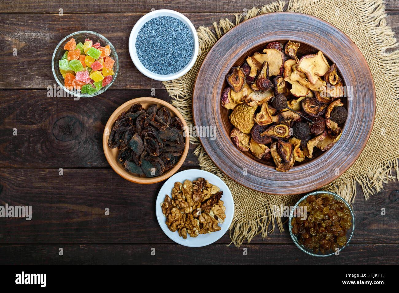 Dried fruit (apples, pears, apricot), berries, walnut kernels, raisins, poppy seeds in a bowl on dark wooden background. - Stock Image