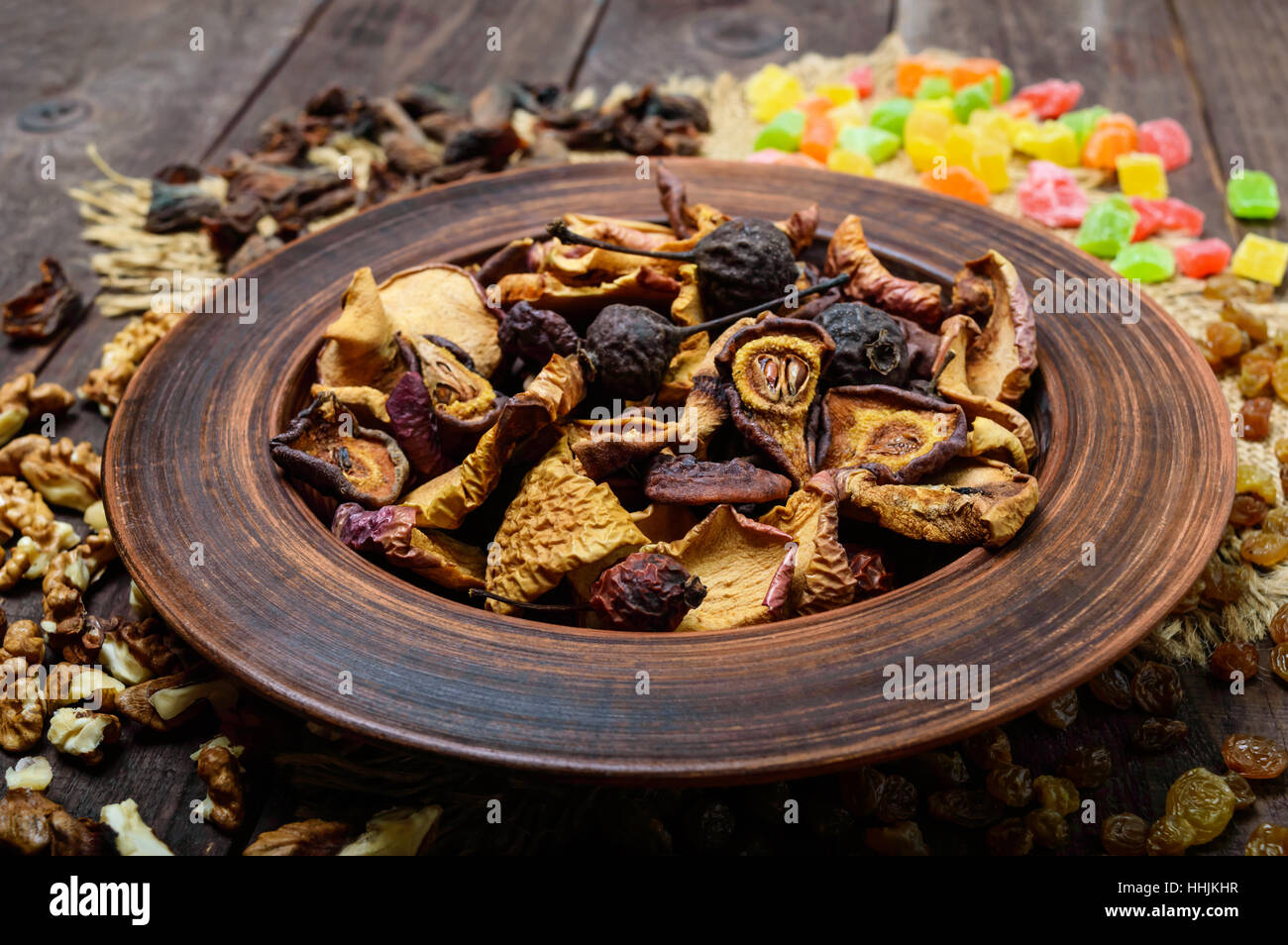 Dried fruit (apples, pears, apricots), berries, raisins and nuts in a bowl on dark wooden background. Close up - Stock Image