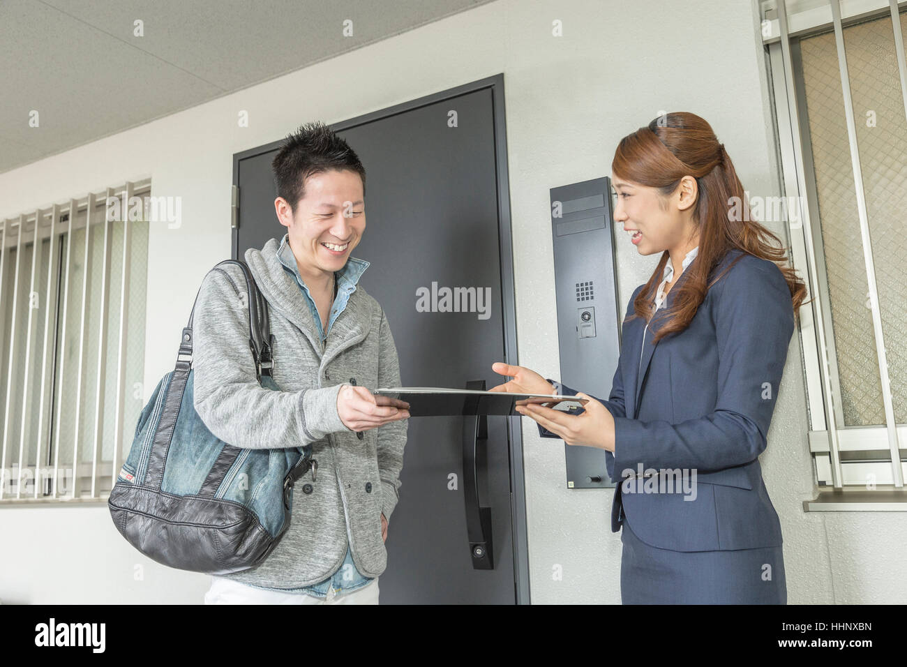 Real Estate Agent Showing Apartment to Buyer - Stock Image