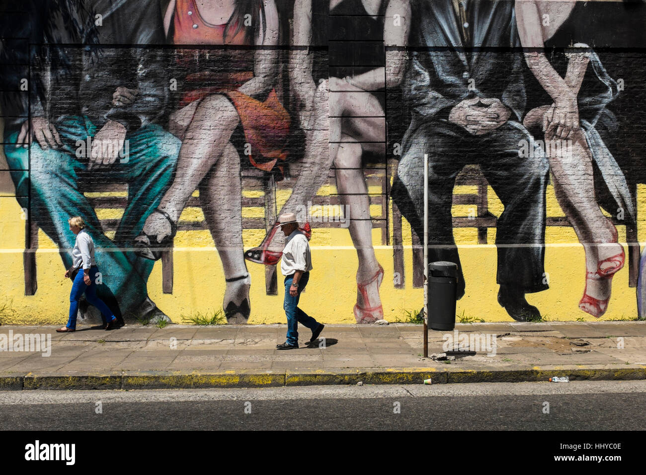 Walking past a city mural depicting sitting couples, Buenos Aires - Stock Image