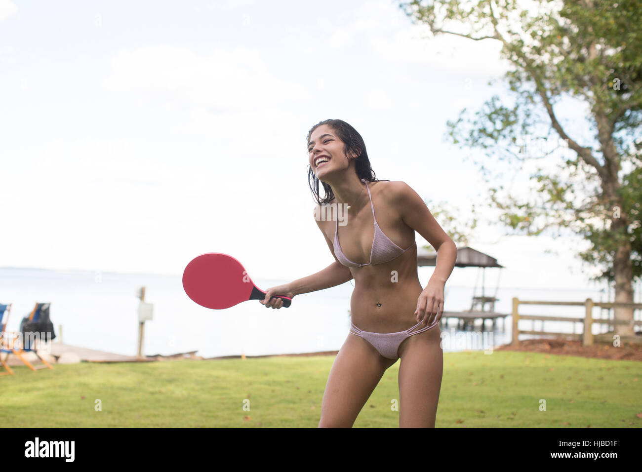 Young woman in bikini playing table tennis at coast, Santa Rosa Beach, Florida, USA - Stock Image