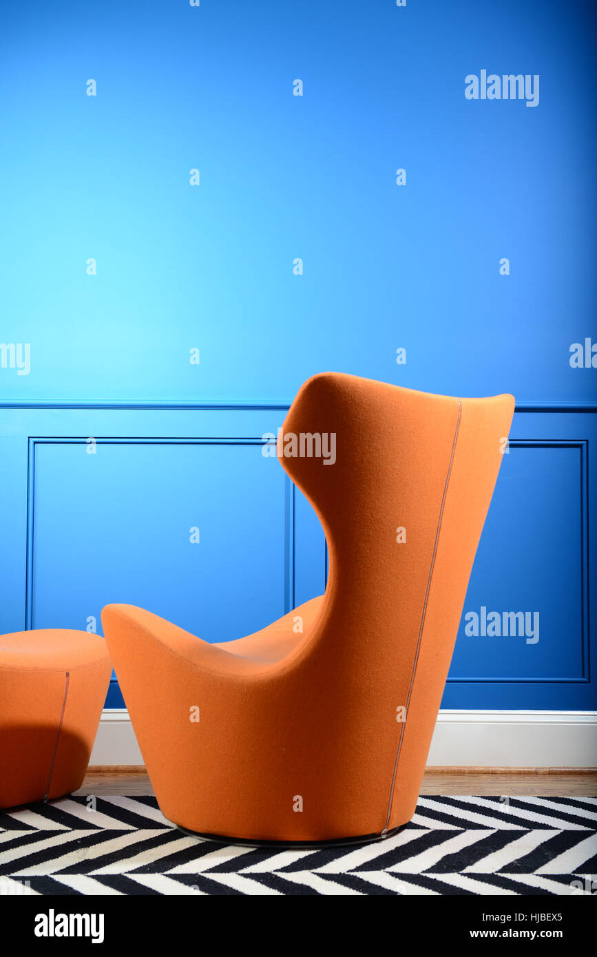 design-modern-retro-orange-chair-and-ottoman-by-blue-wall-HJBEX5.jpg