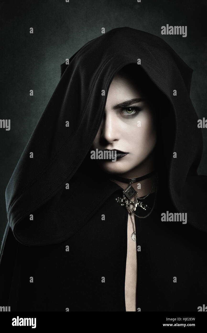 Dark portrait of a beautiful vampire woman with black hood . Halloween and horror concept - Stock Image