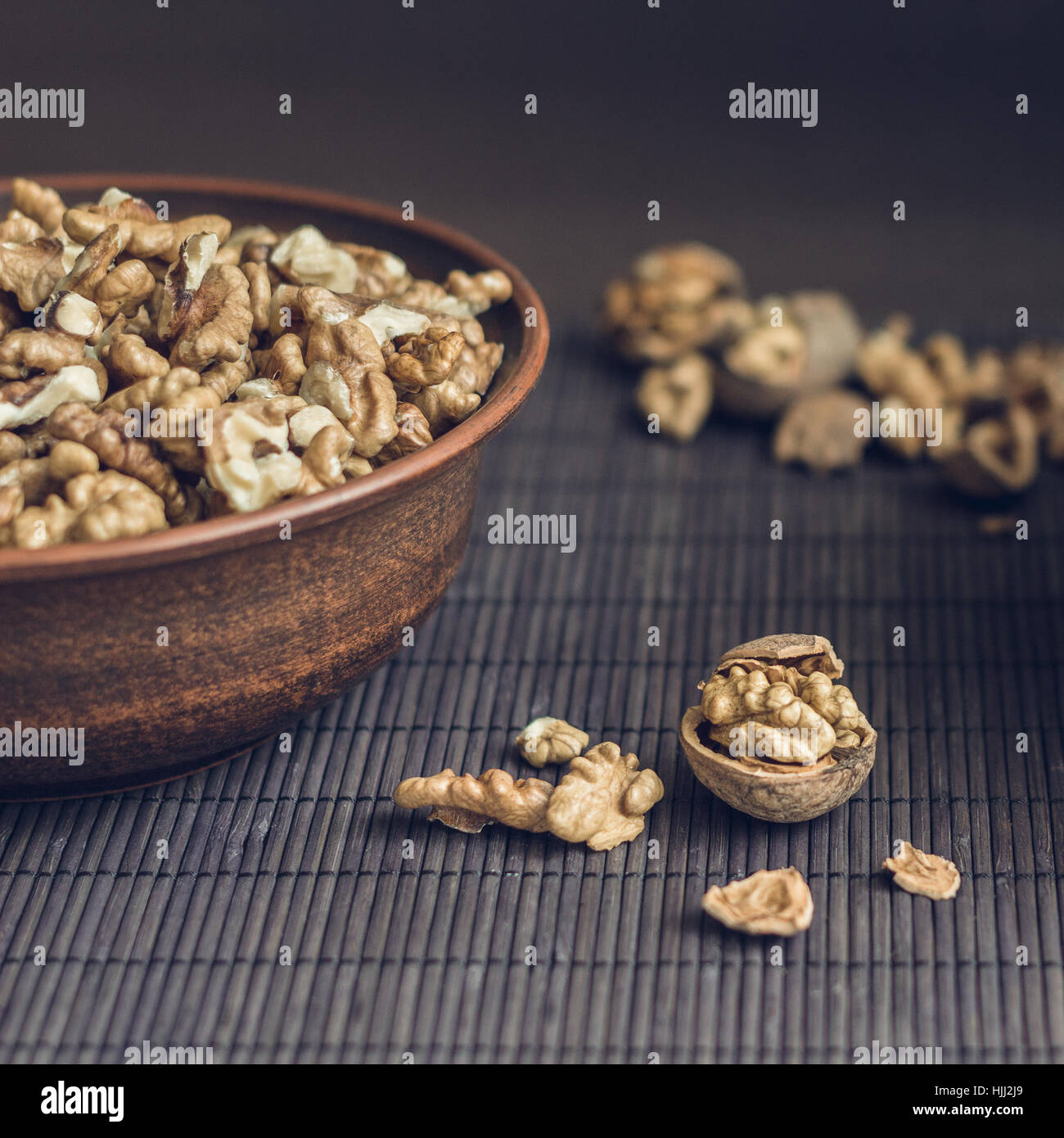 Walnut kernels and whole walnuts in brown ceramic bowl. Healthy organic food concept. Square composition - Stock Image