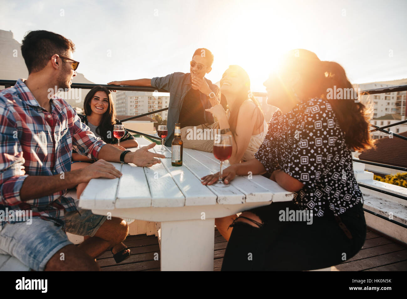 Group of young people sitting around a table  with drinks. Young men and women having rooftop party in evening. - Stock Image