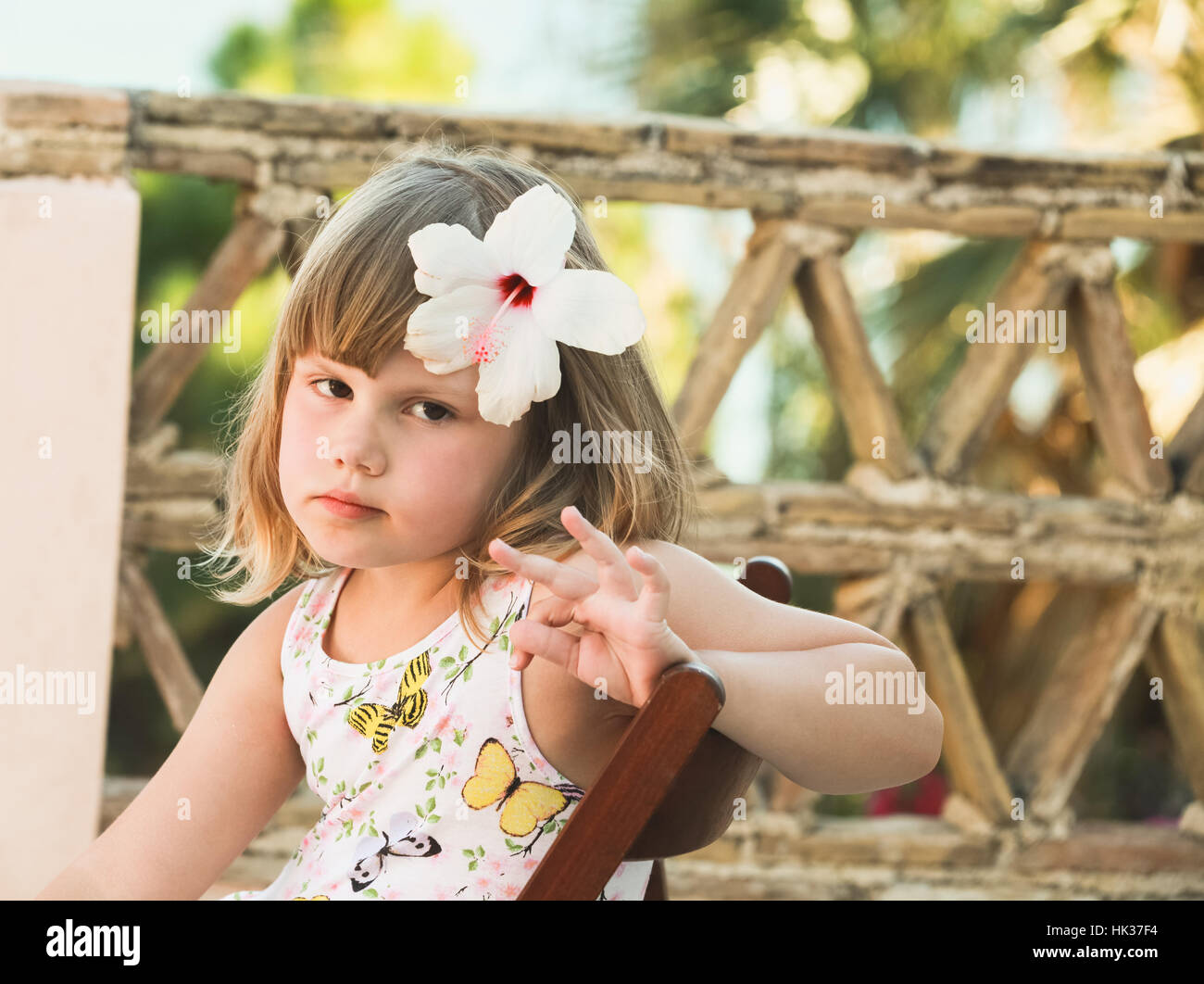 Serious Caucasian Little Girl With White Flower In Hair Outdoor