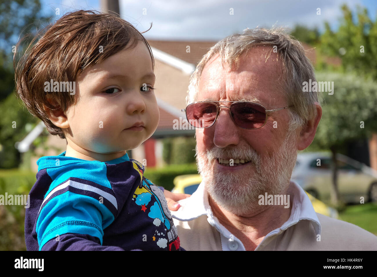 a-smiling-grandfather-holds-his-young-grandson-HK4R6Y.jpg