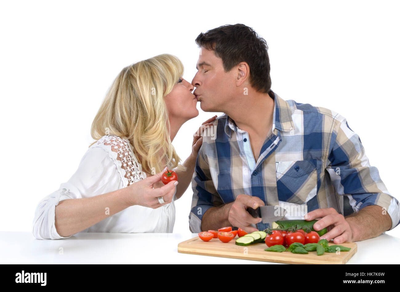 happy mature couple kissing while cooking stock photo: 132319793 - alamy