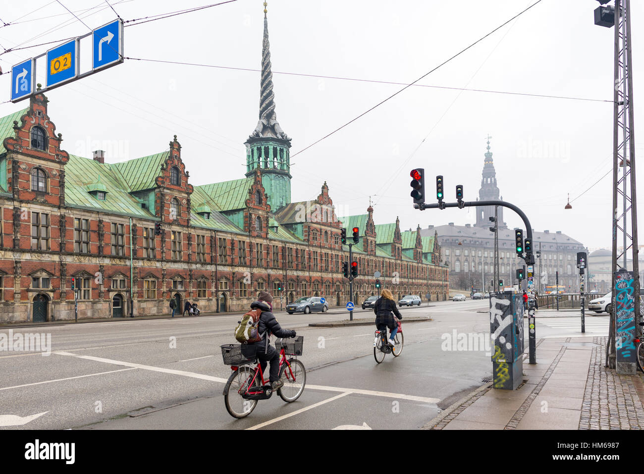 Cyclists pass the Copenhagen Staock Market building, Denmark - Stock Image