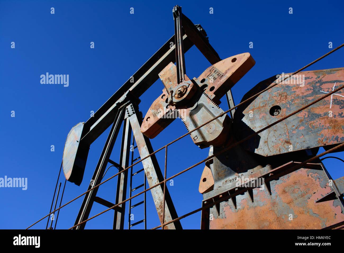 Rusty Oilfield Pumpjack (rocking horse) over a wellhead. Clear blue sky background. Illustrates oilfield life, petroleum - Stock Image