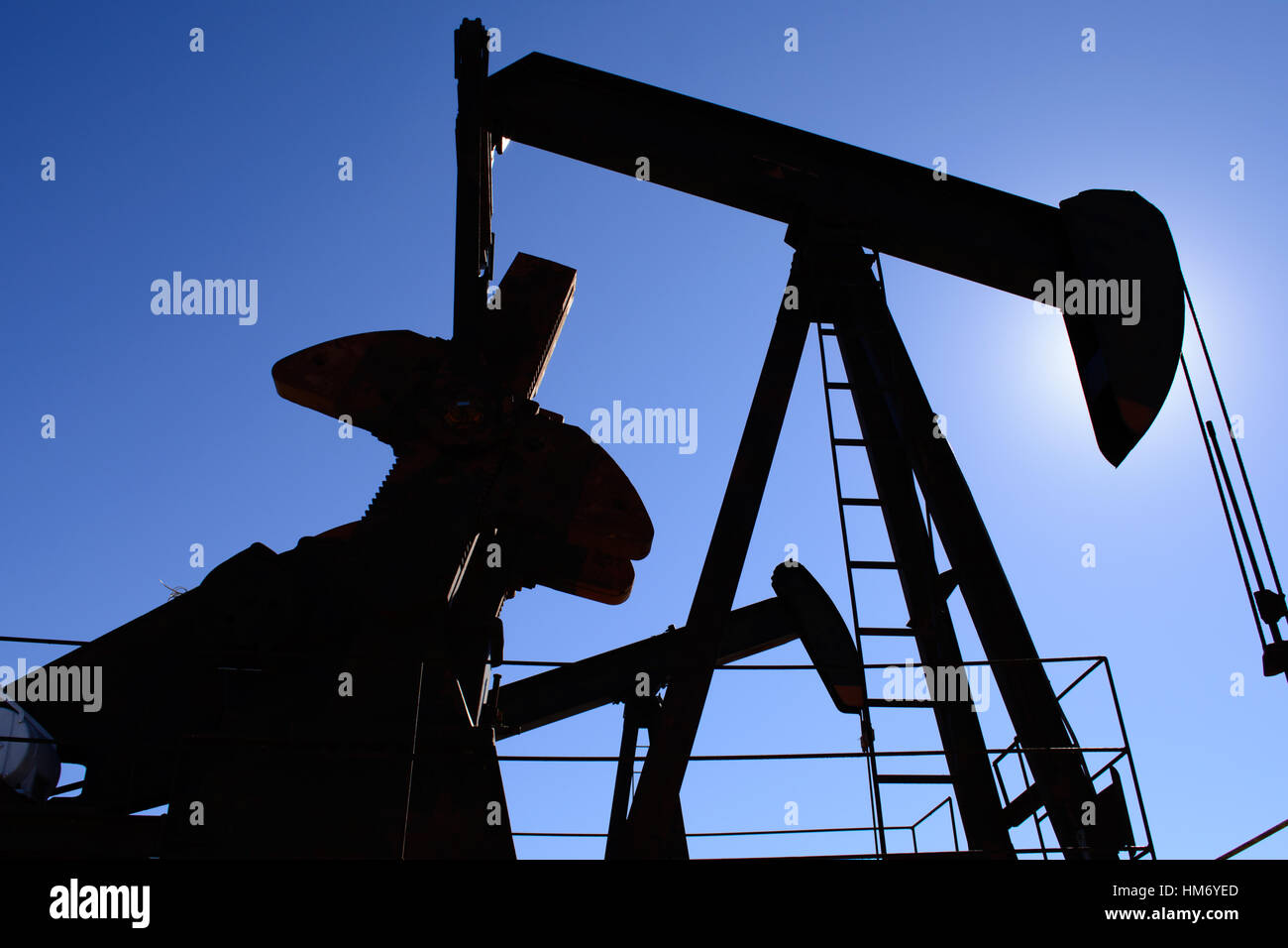 Oilfield pumpjack, rusty and old, silhouetted by the sun. Clear blue sky background. Illustrates oilfield life, - Stock Image