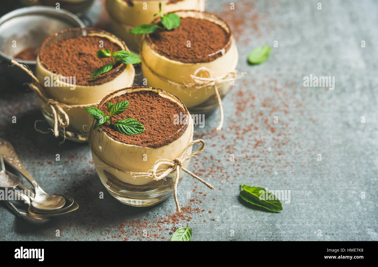 Homemade Italian dessert Tiramisu served in individual glasses with mint leaves and cocoa powder over grey concrete - Stock Image