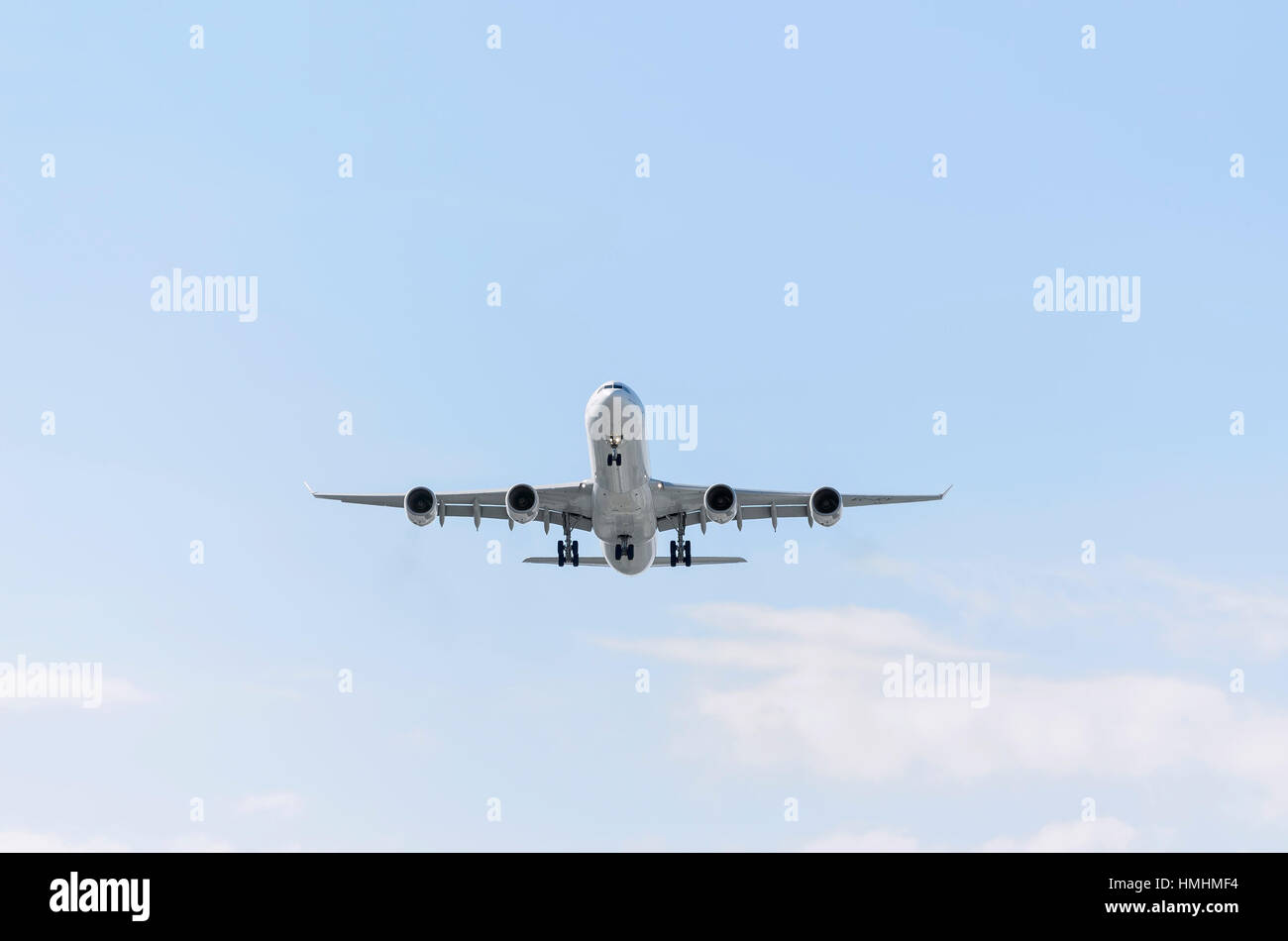 Airplane Airbus A340, of Iberia airline. Blue sky with some clouds. - Stock Image