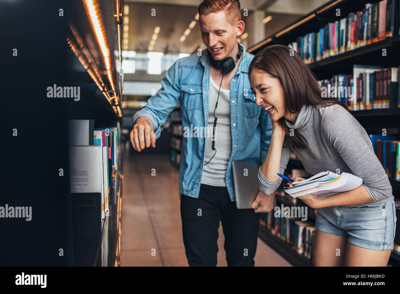 Image of happy young man and woman standing by book shelf in library and looking for books. Students at college - Stock Image