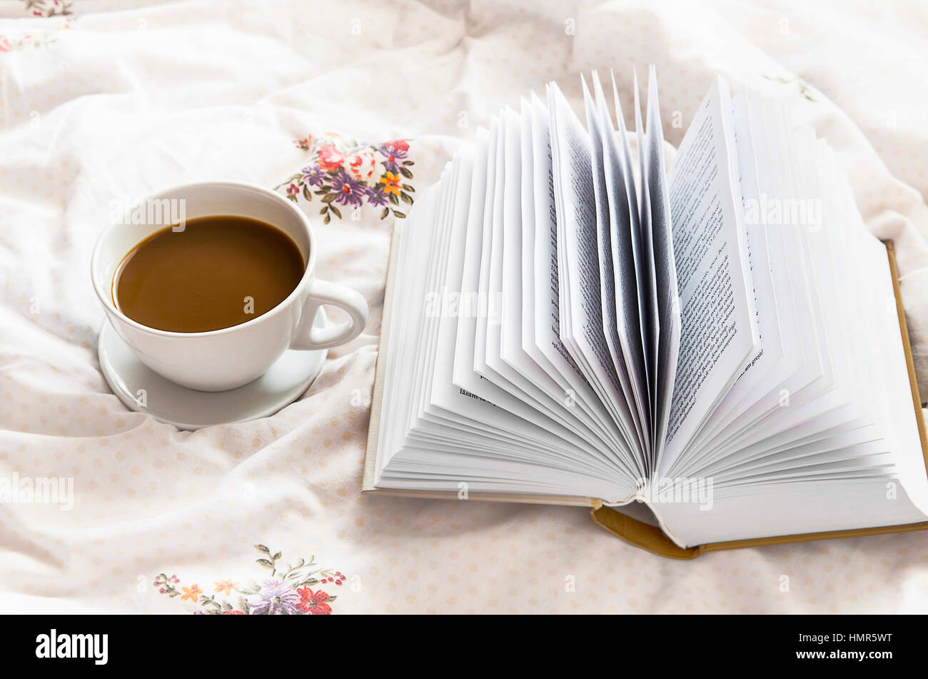 Still Life Coffee Cup And A Book In Bed On Floral Bed Sheets
