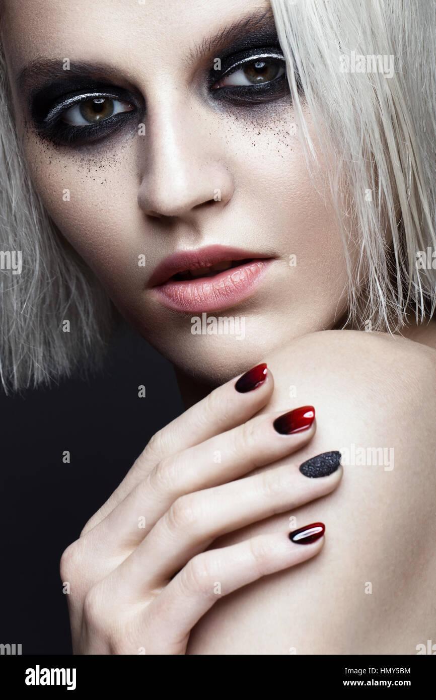 Beautiful blond girl with dark smokey makeup and art manicure design ...