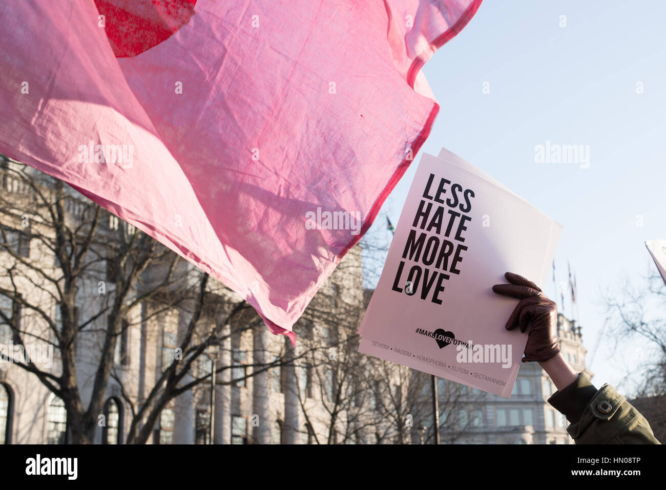 London, UK - 21 January 2017. Hand holding sign saying Less hate more love. Thousands of people protesting in Trafalgar - Stock Image
