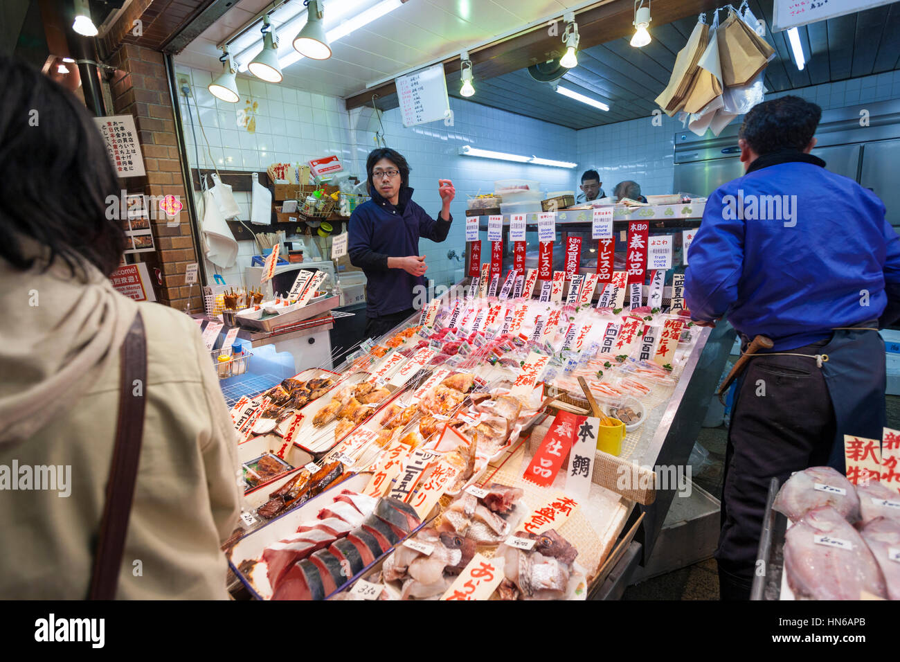KYOTO, JAPAN - MARCH 23: Staff and customers at a stall selling fish in Nishiki food market in Central Kyoto on - Stock Image
