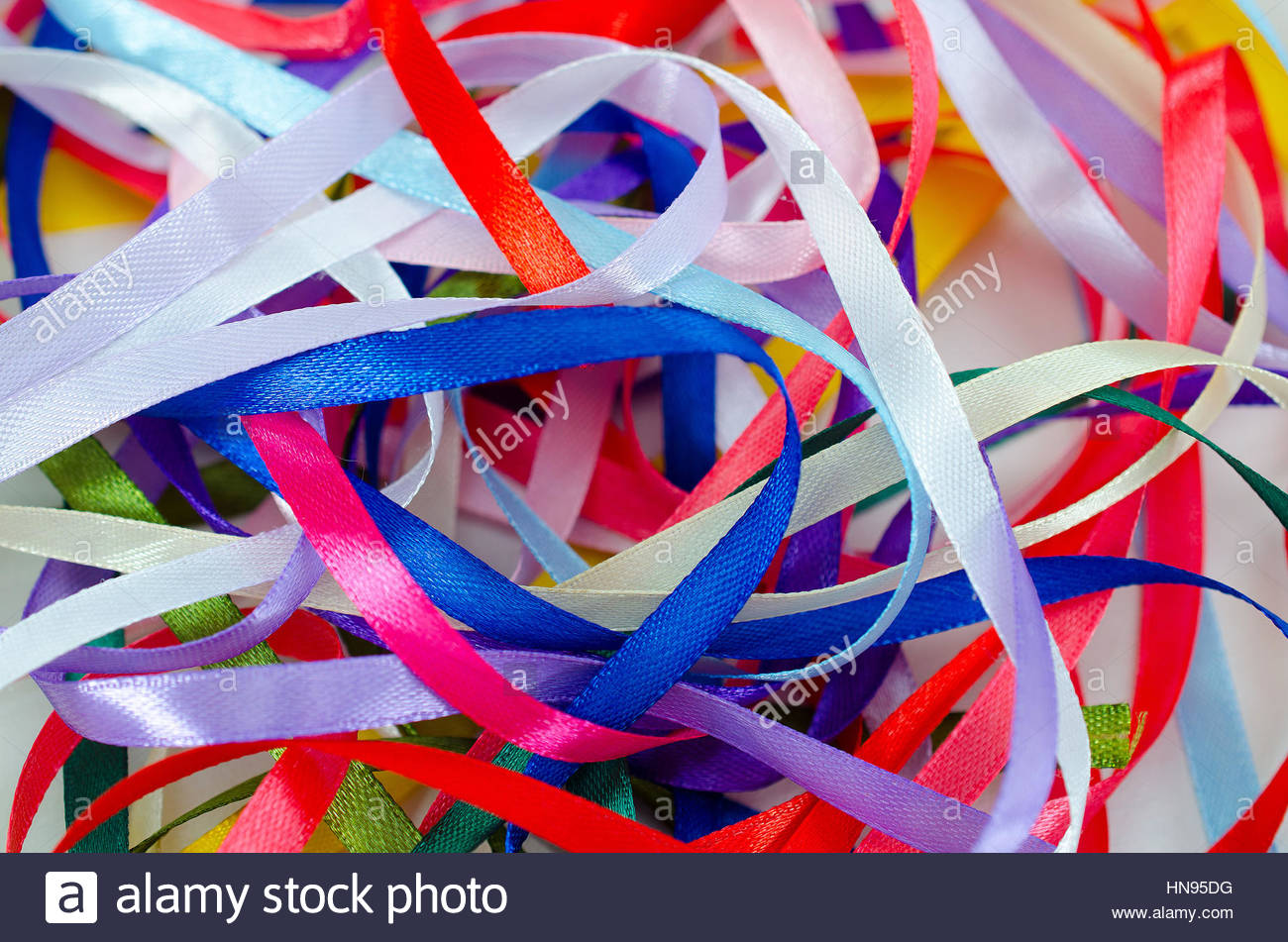 Multi-colored satin ribbons on a white background. Colorful beautiful abstract background. - Stock Image