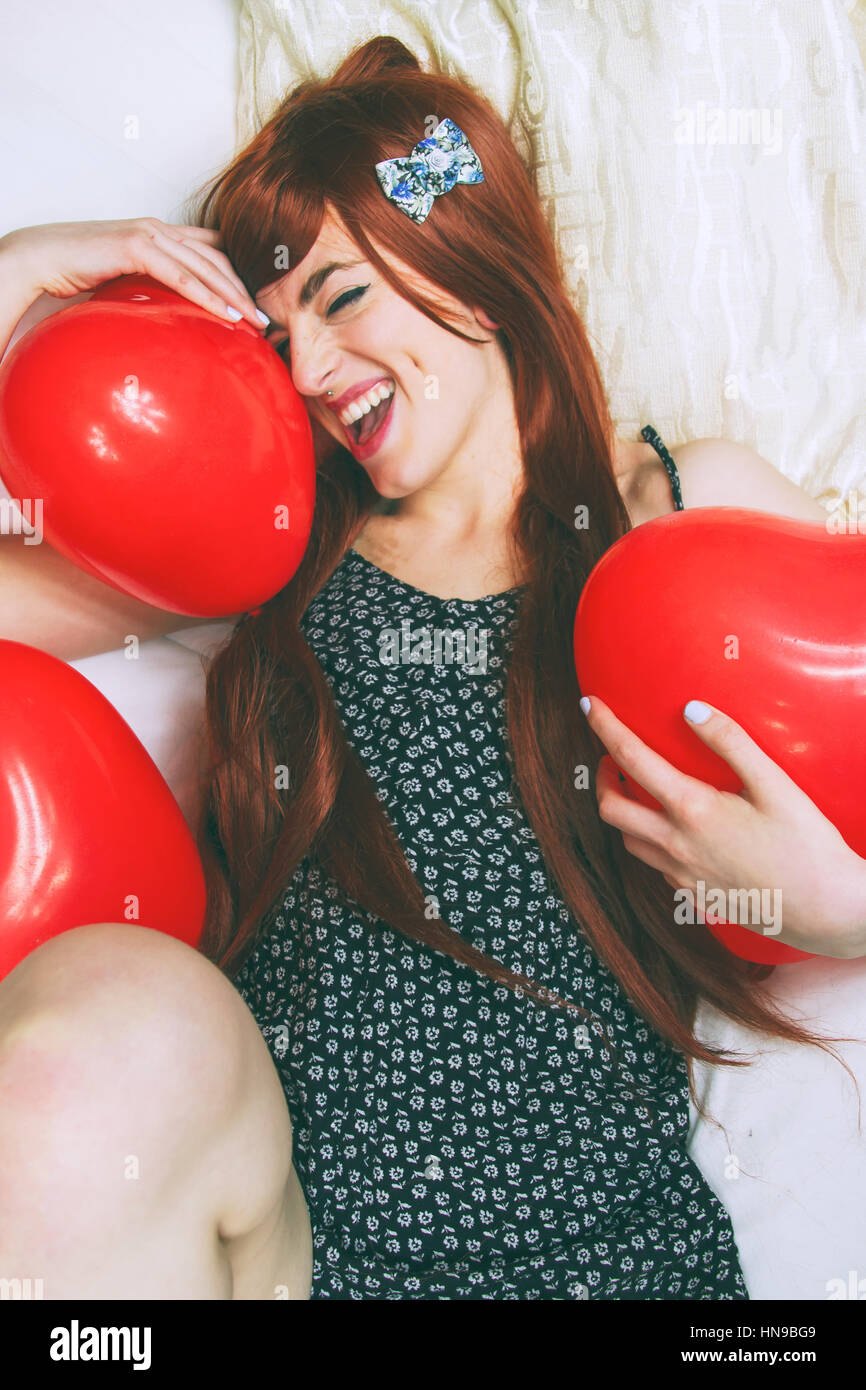 Cheerful young woman with red shaped balloons - Stock Image
