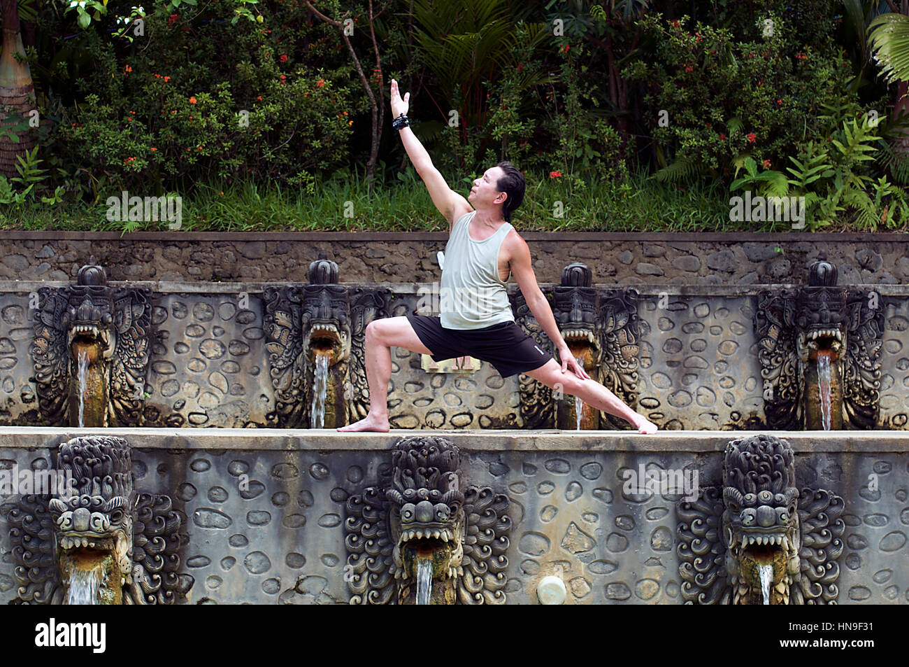 Middle-Aged Asian Man Holds a Hatha Warrior Yoga Pose at Banjar Hot Springs Pools in Bali, Indonesia as Water Pours - Stock Image