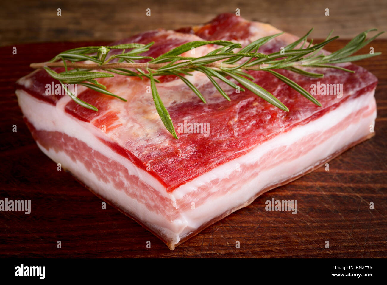 italian bacon pancetta on wooden chopping board - italian food - Stock Image
