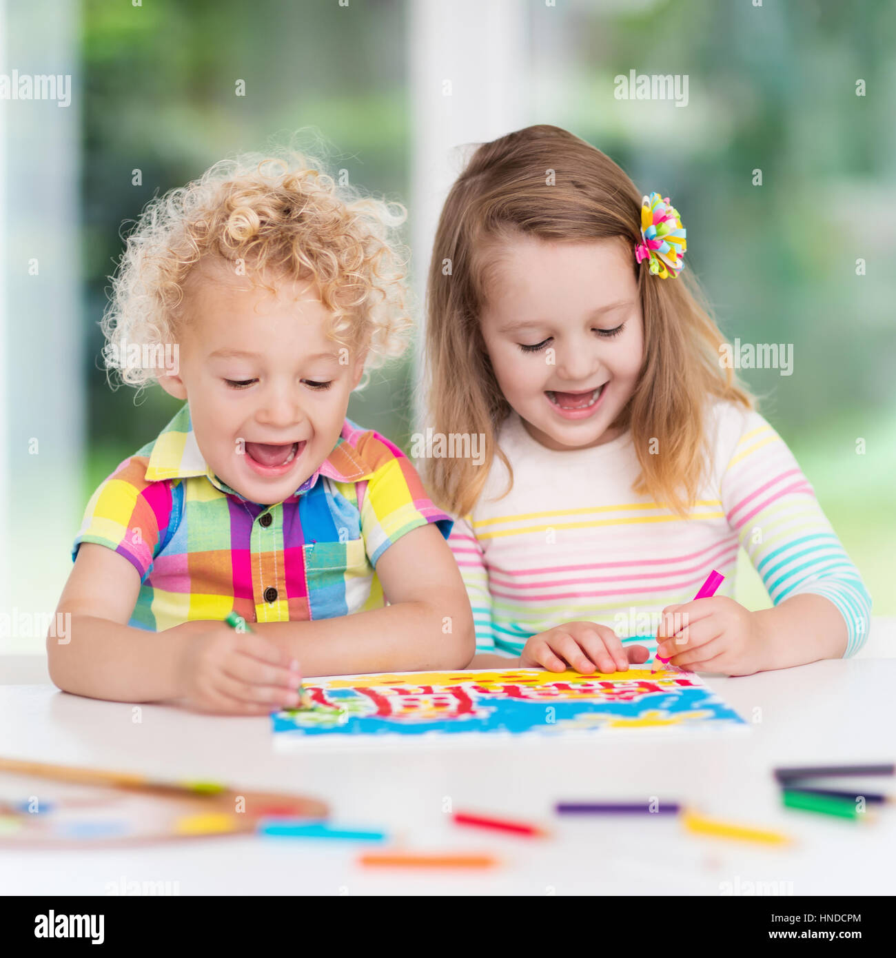 Little Boy And Girl Draw Together In White Room With Window Kids